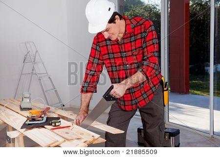 Un trabajador de construcción usando una sierra de madera de mano mientras llevaba un casco de seguridad blanco