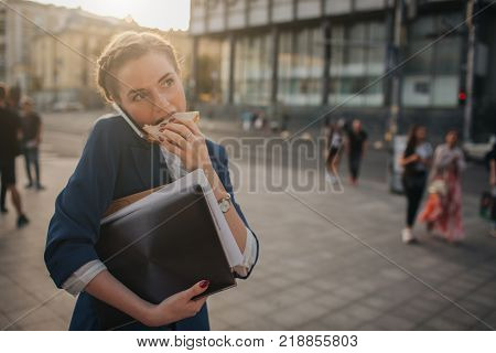 Busy woman is in a hurry, she does not have time, she is going to eat snack on the go. Worker eating and talking on the phone at the same time. Multitasking business person.