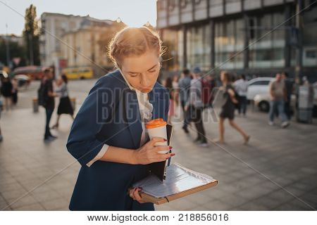 Busy woman is in a hurry, she does not have time, she is going to to drink coffeeon the go. Worker drinking and talking on the phone at the same time. Businesswoman doing multiple tasks. Multitasking business person.