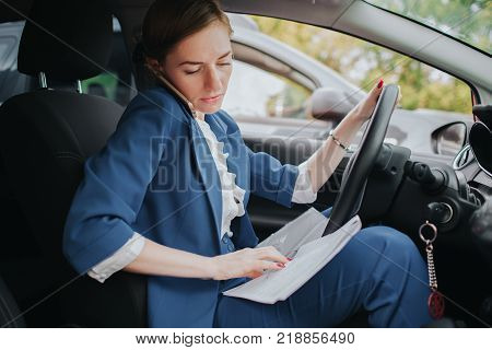 The driver going on the road, speaking on the phone, working with documents at the same time. Businesswoman doing multiple tasks. Multitasking business woman.