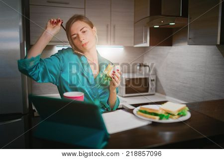 Busy woman eating, drinking coffee, talking on the phone, working on tablet at the same time. Businesswoman doing multiple tasks. Multitasking business person. Freelancer works at night.