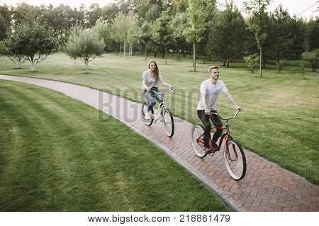 Closer view of a two non-professional bikers that like to ride from time to time. They decided to choose a nice and smooth road in the middle of park to ride alone end enjoy the small travel.