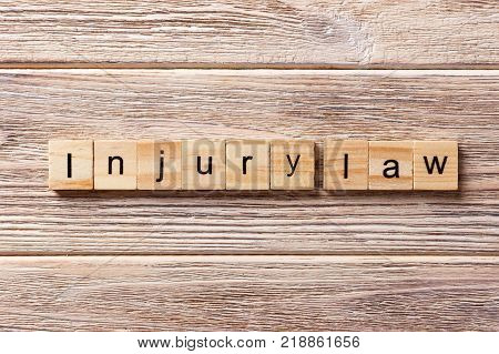INJURY law word written on wood block. INJURY law text on table concept.
