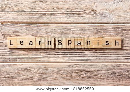 learn spanish word written on wood block. learn spanish text on table concept.