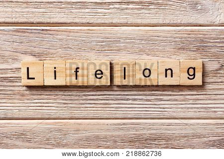 life long word written on wood block. life long text on table concept.