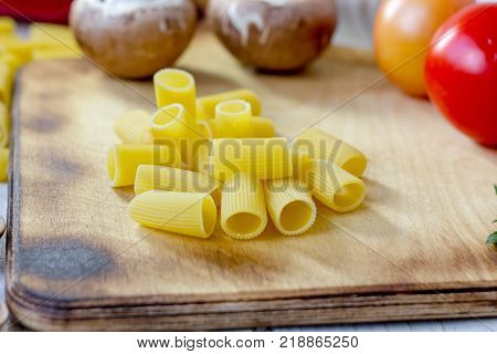 Dry rigatoni pasta on wooden kitchen board with vegetables