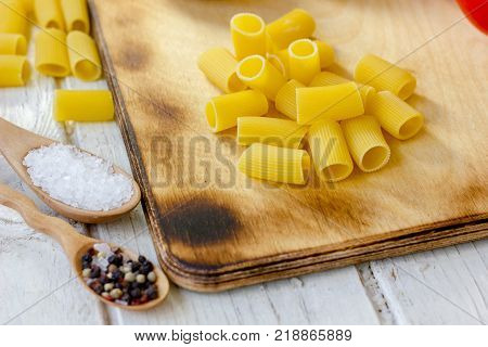 Dry rigatoni pasta on wooden board surrounded by vegetables
