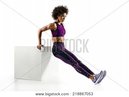 Triceps dips. Sporty girl doing exercises for triceps on white background. Fitness and healthy lifestyle concept