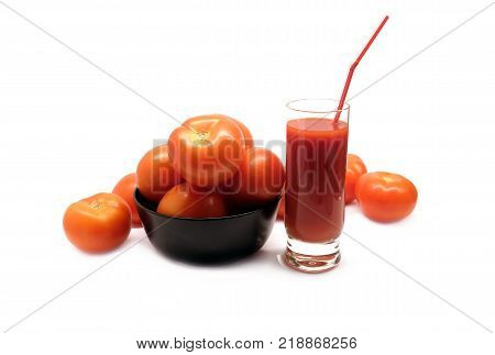 Big glass with tomato juice with drinking strawand many ripe tomatoes in round black bowl studio shot isolated on white background