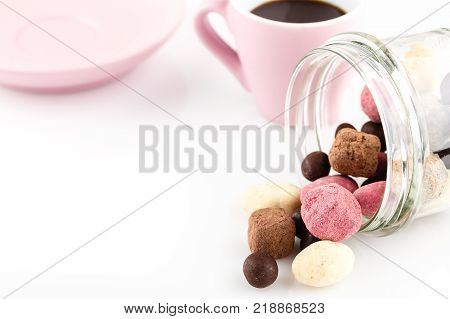Сolorful handmade candies in glass jar and pink cup of coffee on white background with copy space. Valentines day concept