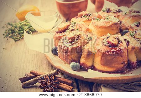 Homemade delicious cinnamon rolls with lemon and berries over wooden background