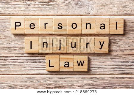 personal injury law word written on wood block. personal injury law text on table concept.