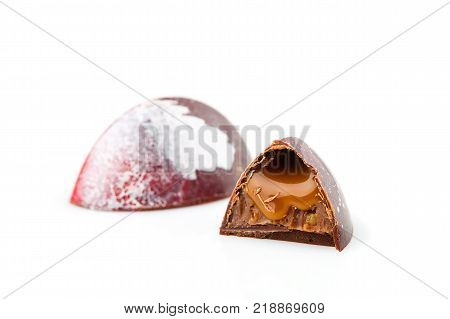 Cut handmade chocolate candy with ganache and caramel isolated on white background. Exclusive handcrafted bonbon. Product concept for chocolatier