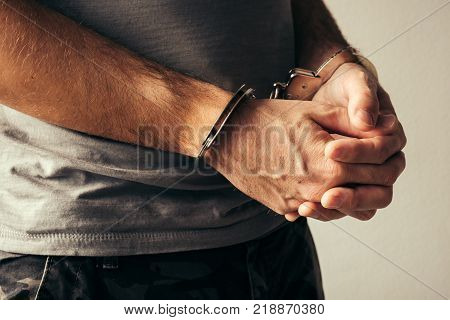 Handcuffed soldier in military army clothes. Prisoner of war or arrested terrorist close up of hands in handcuffs selective focus.