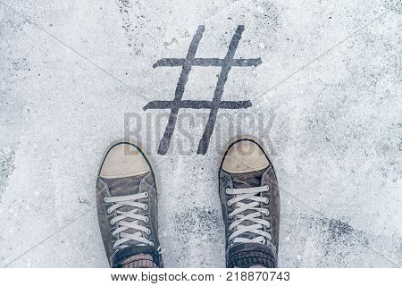 Feet standing over hashtag imprint on street social media and networking concept