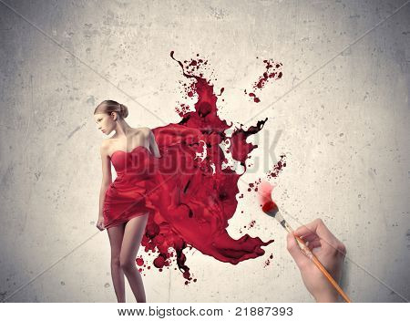 Man's hand painting the elegant dress of a beautiful woman