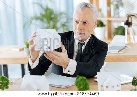 Lovely house. Smart experienced worker of a real estate agency looking attentively at the nice realistic miniature of a house while sitting in his office