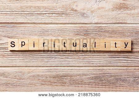 Spirituality word written on wood block. Spirituality text on table concept.