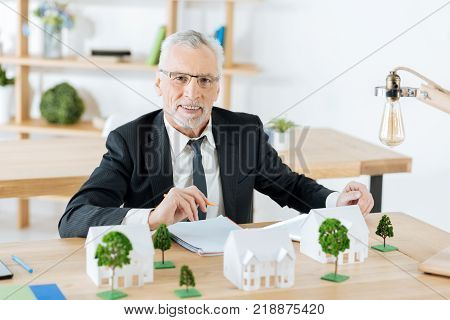 Productive day. Enthusiastic emotional real estate agent feeling good while being at work and sitting at the table with a pencil in his hand