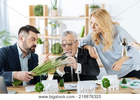 Interesting material. Emotional enthusiastic real estate agents looking curious while touching a bunch of synthetic grass and discussing its usage near one of their gorgeous houses