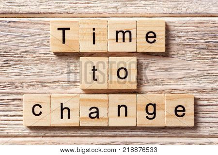 TIME TO CHANGE word written on wood block. TIME TO CHANGE text on table concept.