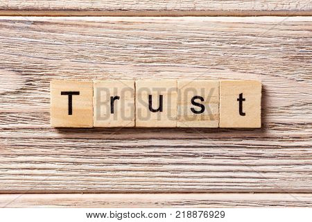 TRUST word written on wood block. TRUST text on table concept.