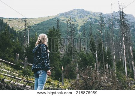 Young blonde girl looking at fallen trees in spring forest on background of mountains