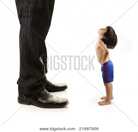 Little small child  is looking at the giant legs of  businessman adult