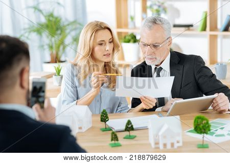 Look here. Clever skilled reliable worker looking concentrated while sitting with her older colleague and showing him an important part of a document poster
