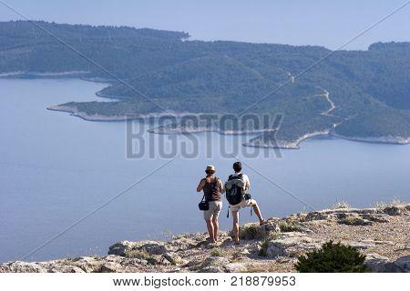Tourist couple looking at Hvar island from Vidova Gora on island Brac