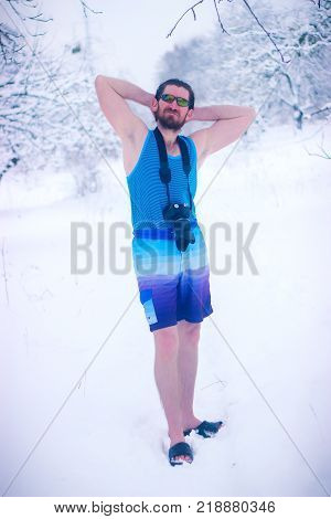 Man with glasses and camera enjoying snow bath outdoor after hot sauna. Healthy treatment.