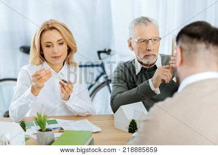 Scrupulous work. Attentive calm clever scientists being very careful while holding test tubes and looking at the tiny growing plants in them poster