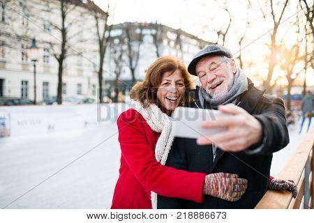 Happy senior couple with smartphone on a walk in a city in winter. A man and woman taking a selfie.