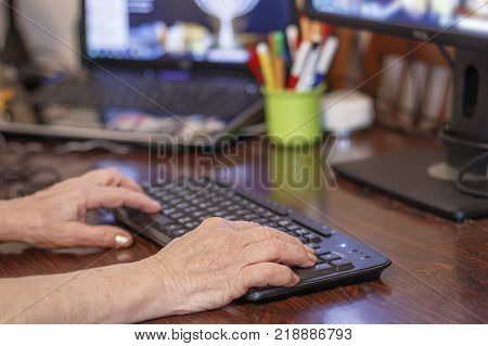 Hands of an elderly woman typing on a computer keyboard