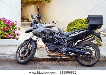 Sport motorbike parked on narrow touristic street. Resort town Rethymno in Greece. Mediterranean architecture on island Crete