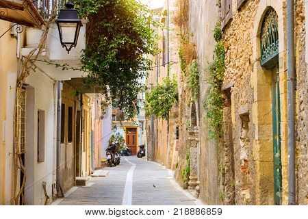 Walk around the old resort town Rethymno in Greece. Architecture and Mediterranean attractions on island Crete. Narrow touristic street with parked scooters