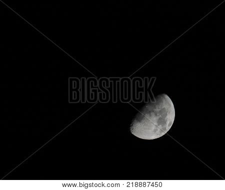 tilted half moon in a dark sky with shadows on craters