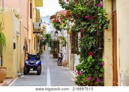 Narrow touristic street with parked Quad Bike and scooter. Walk around the old resort town Rethymno in Greece. Architecture and Mediterranean attractions on island Crete