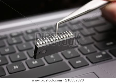 Hand with tweezers holds the chip above the keyboard of the laptop