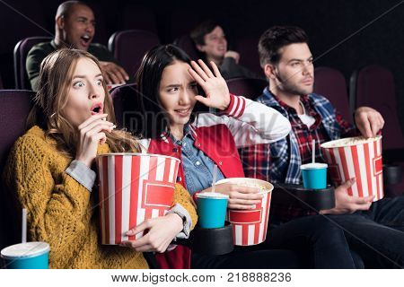 scared friends with popcorn and soda watching horror movie in cinema