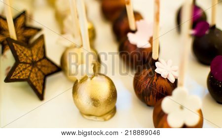 Rich Chocolate dessert photography with chocolate cake pops made of chocolate and fudge with white chocolate flowers and dark chocolate art and chocolate stars for dessert conceptual background