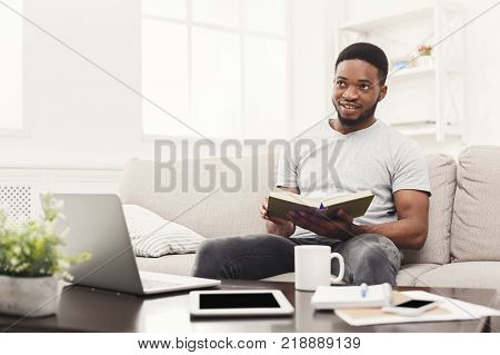 Happy young man at home reading interesting book, sitting on beige couch in light livingroom, copy space poster