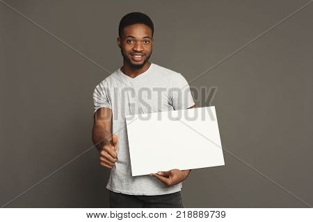 Picture of young smiling african-american man holding white blank board and showing thumb up on grey background, copy space