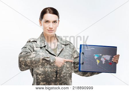 Game plan. Ambitious earnest nice woman staring at the camera   and posing on the isolated background while demonstrating  map