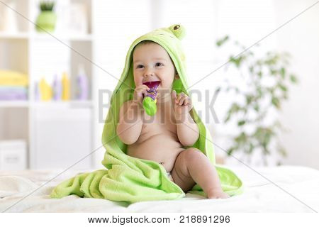 Little baby boy in green towel biting toy after bath. Infant boy with teether. Child health care.
