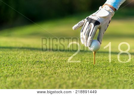 Golfer asian woman putting golf ball for Happy New Year 2018 on the green golf copy space. Healthy and Holiday Concept.