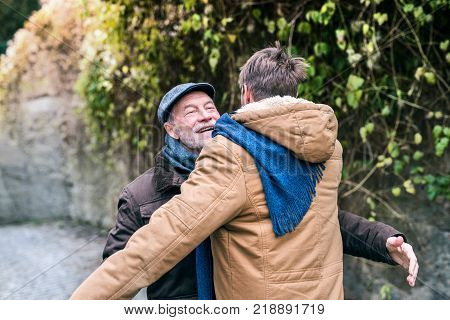 Senior father and his young son on a walk in town, hugging.