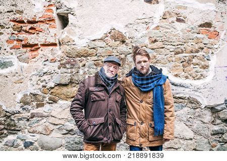 Senior father and his young son on a walk in town. Two men standing against an old brick wall.