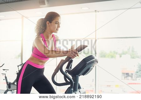 Young woman on elliptical trainer. Cardio workout in gym, healthy lifestyle, copy space