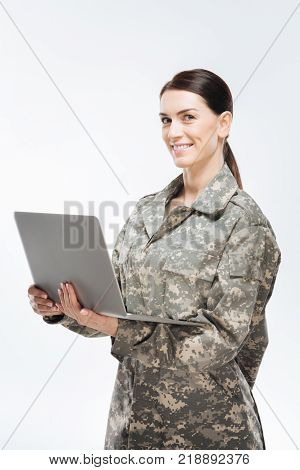Computerized security. Young cheerful appealing woman in fighting uniform gazing at the camera  while posing on the background and bringing laptop